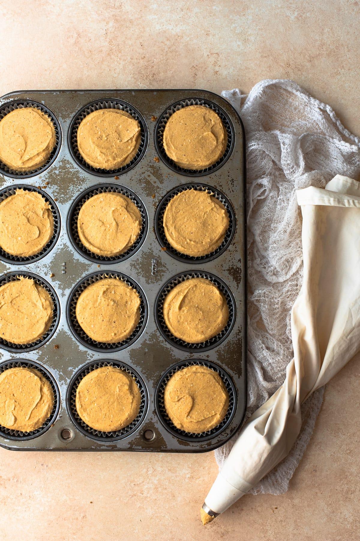 Mini pumpkin cheesecakes assembled in a muffin pan.