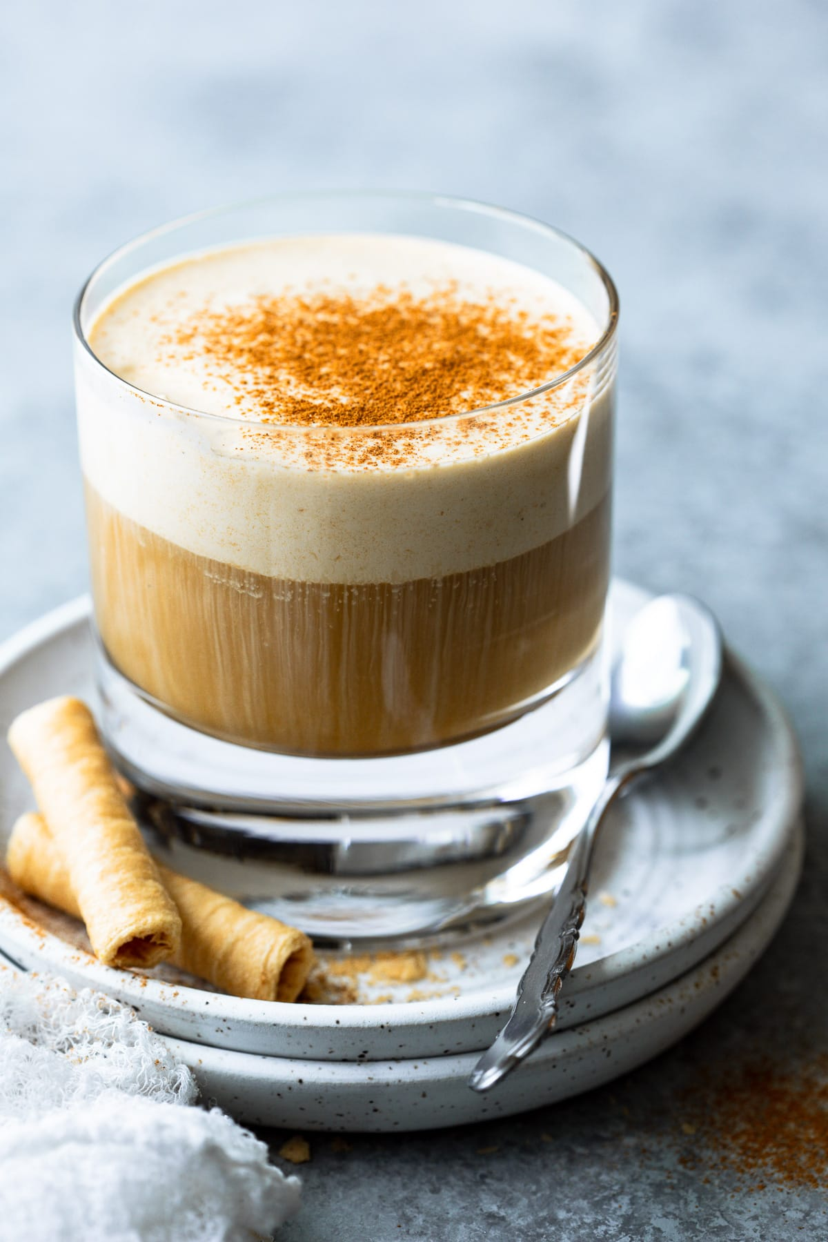Coffee with pumpkin cold foam in a glass, on top of two stacked plates.