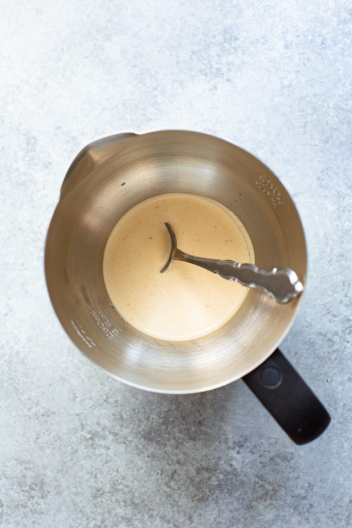 Pumpkin cream cold foam in a milk frother.