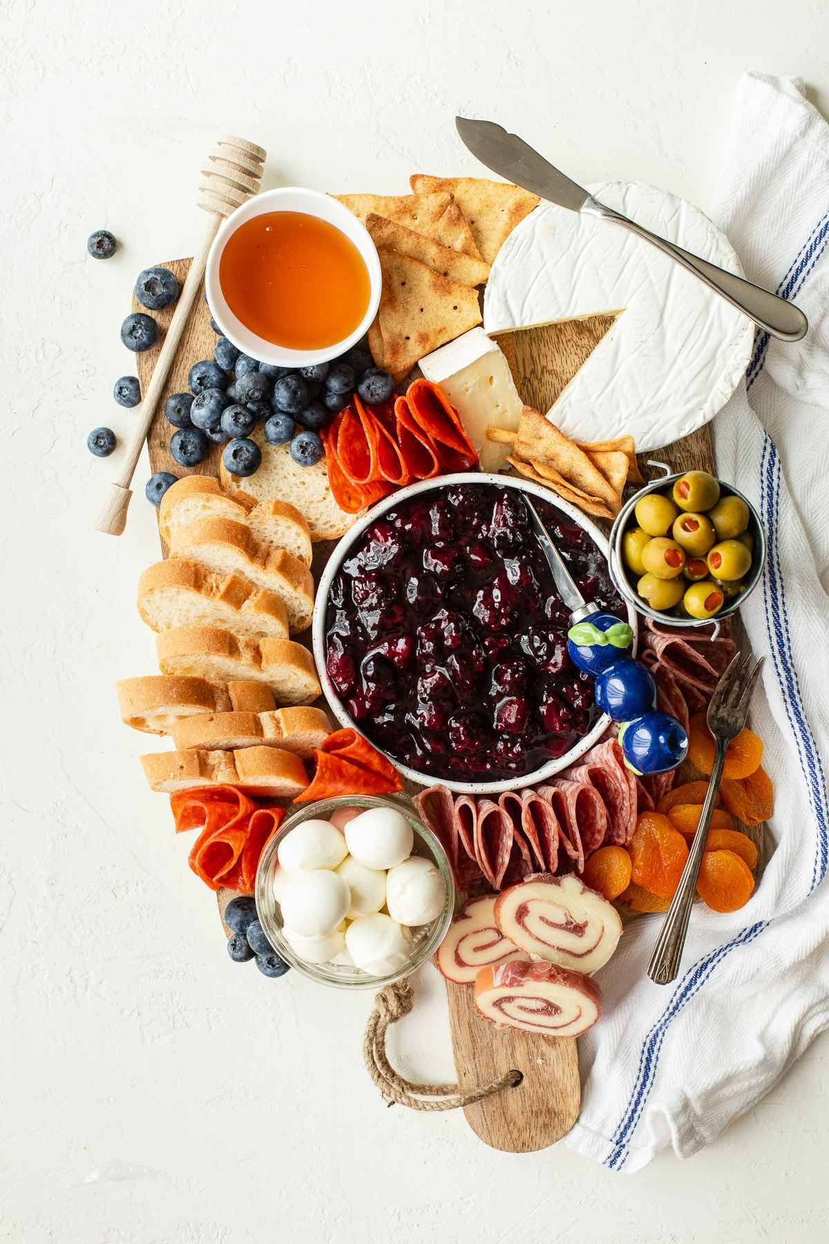 Charcuterie board with a variety of meats, cheeses, crackers, and bread, plus homemade fruit compote.