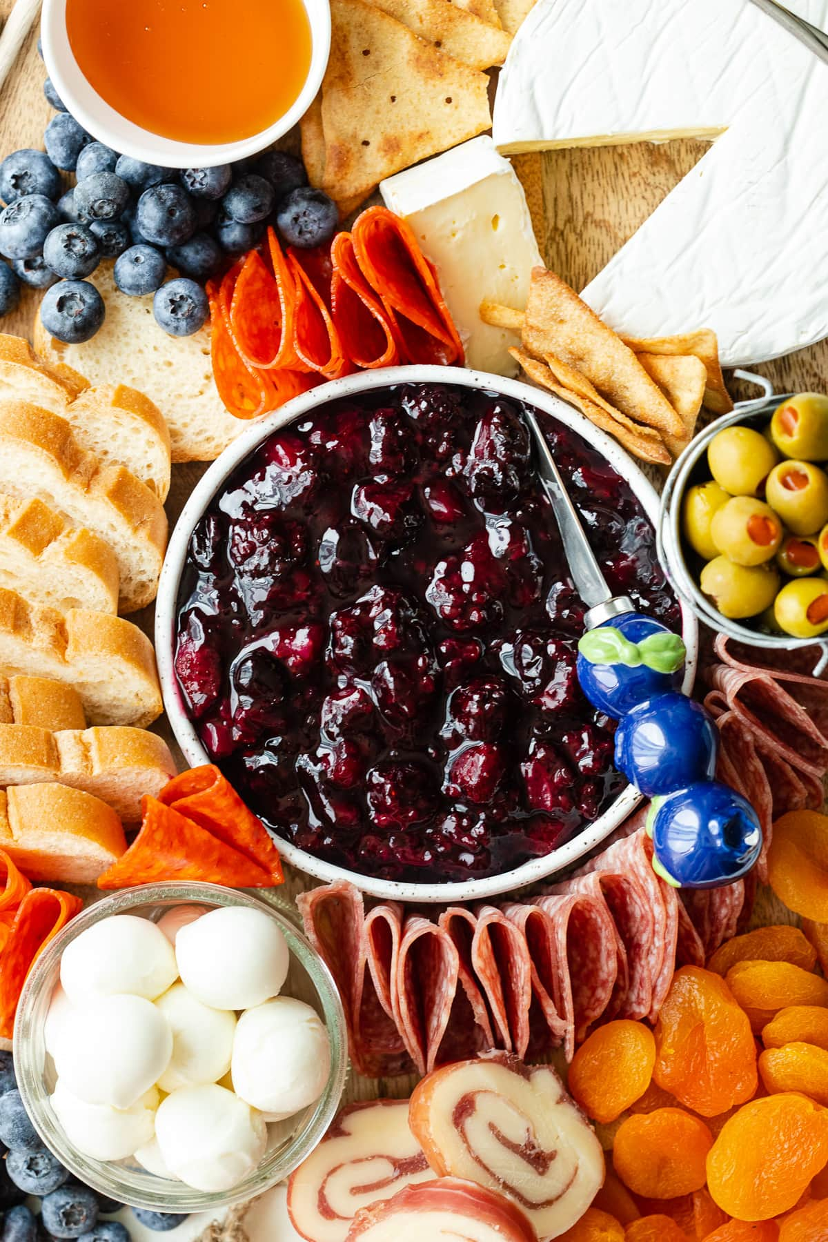 Close up of a charcuterie board with a bowl of berry compote in the center.